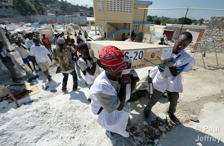 Emergency workers of Norwegian Church Aid, a member of the ACT Alliance, carry a 10,000 liter water bladder into a makeshift tent city in the yard of a partially destroyed school in the Pean district of Port-au-Prince, the capital of Haiti, which was ravaged by a January 12 earthquake.