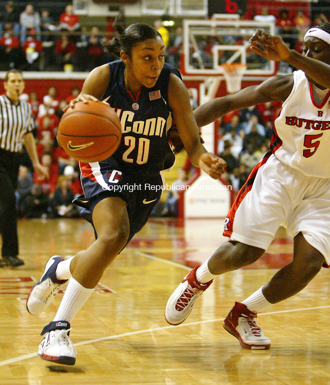 PISCATAWAY, NJ, 02/26/07- 022607BZ08- UConn's Renee Montgomery (20) drives past Rutgers's Essence Carson  (5)<br />  during their game at Rutgers Monday night. <br /> Jamison C. Bazinet Republican-American