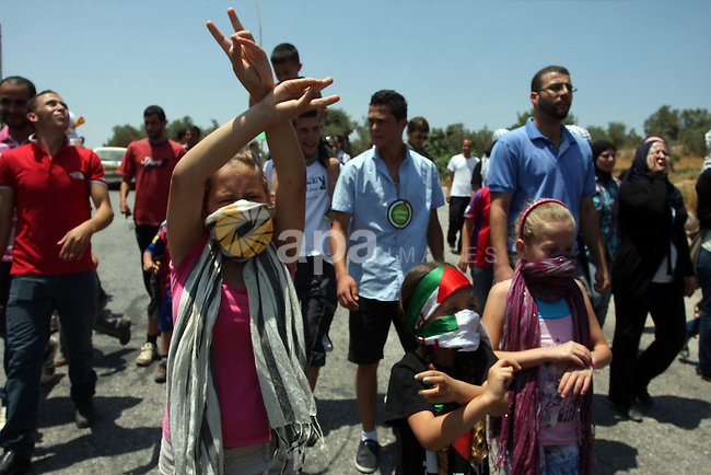 A Palestinian protestor raises the victory sign during a demonstration against Israel's separation barrier in the West Bank village of Nabi Saleh near Ramallah, , Friday, June 29, 2012. Palestinians protest weekly against the neighbouring Jewish settlement of Halamish. Photo by Issam Rimawi