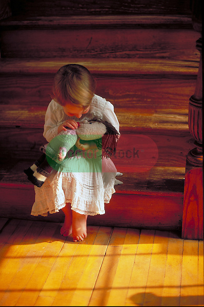 young girl sitting on stairs kissing doll