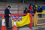 Visiting fans tying a flag to railings at Wincham Park, home of Witton Albion before their Northern Premier League premier division fixture with Warrington Town. Formed in 1887, the home team have played at their current ground since 1989 having relocated from the Central Ground in Northwich. With both team chasing play-off spots, the visitors emerged with a 2-1 victory, the winner being scored by Tony Gray in second half injury time, watched by a crowd of 503.