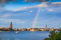 Regnbåge och sol över Riddarholmen och Stadshuset i Stockholm