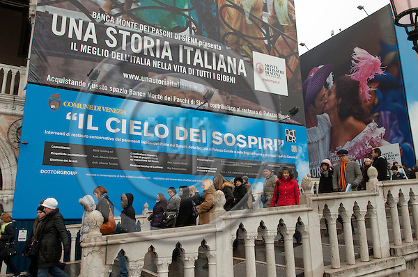 San Marco-Venice-Italy - January 09, 2011 -- Tourists on Ponte della Paglia, passing big panels with advertisement of a sponsor (Italian bank) on the facade of the Doge's Palace; the bank helps to restore the Palace -- tourism, people -- Photo: Horst Wagner / eup-images