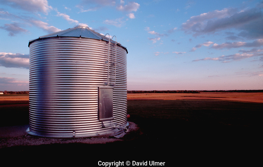 Galvanized steel grain bin reflects sunset on Illinois farm