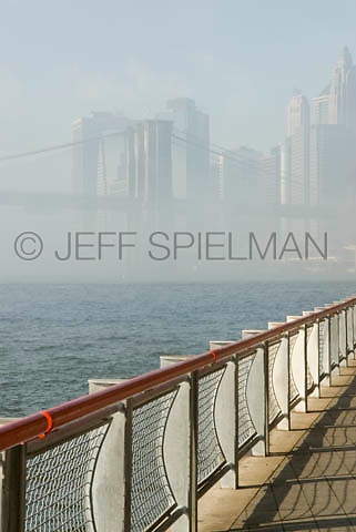 THIS IMAGE IS AVAILABLE EXCLUSIVELY FROM CORBIS....Please search for image # 42-19639564 on www.corbis.com....Brooklyn Bridge, East River and Lower Manhattan Skyline on a Foggy Morning, Viewed from the East River Esplanade....New York City, New York State, USA