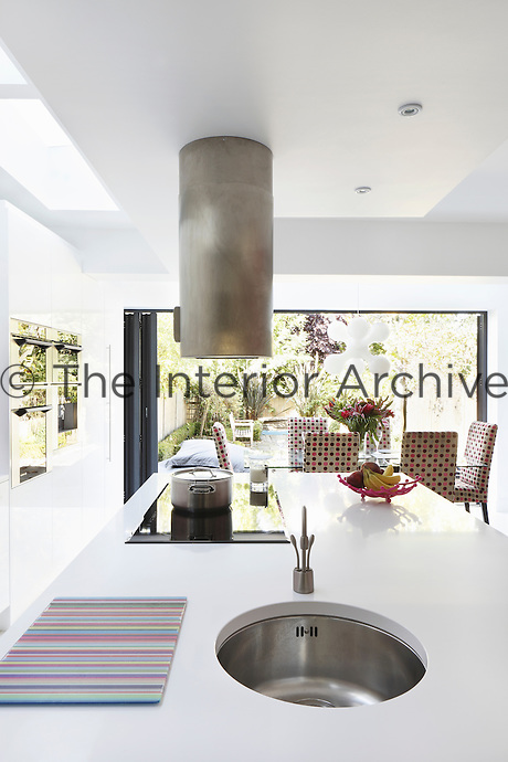 The kitchen/dining area is dominated by a large kitchen island which contains a sink and a ceramic hob