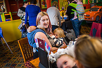 A mother sitting at a table breastfeeds her two year old daughter with her twelve week old baby asleep in a sling on her back.in the family restaurant and play area of a pub.<br /> <br /> Lancashire, England, UK<br /> <br /> Date Taken:<br /> 07-01-2015<br /> <br /> &copy; Paul Carter / wdiip.co.uk