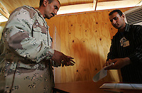an iraqi soldier hands from 3d battalion, 1st brigade, 2nd Iraqi Army division hands his voting sheet to a poling official while voting in the Iraqi National elections at their base in Camp Rmadi at a pol site under the administration of the Indipendent Electoral Commision of Iraq on Mon Dec 12 2005. At the end of the day about 2000 soldiers will vote at this site according to An Iraqi official.