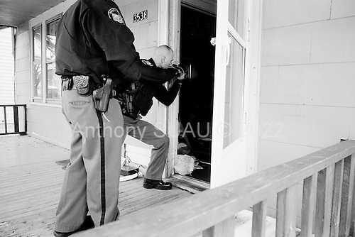 Cleveland, Ohio.March 25, 2008 ..Delivering warning and final eviction notices Detective Robert Kole of the Cuyahoga County Sheriff's Department enters every situation with caution. When the residents are at the home he must assure that all is final and that the home is clear of weapons and that the residents are indeed moving out. ..If no one is there, then he must authorize that the door be forcibly open. He then enters and clears the house at gunpoint in hopes that there are no squatters or inhabitants threaten himself or the movers. He also clears the house for weapons...All emotions and fears are on the surface as some residents greet him by crying on his shoulder while others can threaten him with a weapon...In this intercity Cleveland home another Sheriff calls for back up after a home is found abandon and the front door is found open. The decomposing body of a dog, tied to a leash to starve to death, is found in the kitchen.
