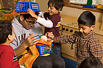 Preschool New York City ages 4-5 high school student volunteering in the classroom interacting with group of boys.