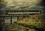 Old train crossing a bridge under stormy sky