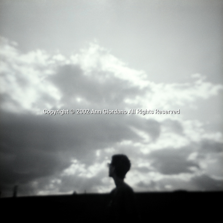 Silhouette of woman with glasses looking at sun behind clouds