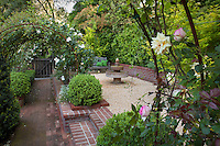 Secret garden room with bench and fountain next to brick path under rose covered pergola