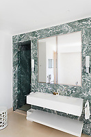 Verde Antigua stone decorates the bathroom. The basin and shelf were designed by C-Z and made in Corian.