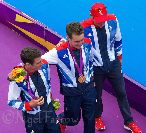 07 AUG 2012 - LONDON, GBR - Great Britain team members Jonathan Brownlee (left), Alistair Brownlee (centre) and Stuart Hayes walk away from the medal ceremony after Alistair Brownlee had won the men's London 2012 Olympic Games Triathlon in Hyde Park in London, Great Britain (PHOTO (C) 2012 NIGEL FARROW)
