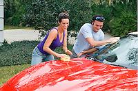 Young Couple in their 30s having fun washing car.