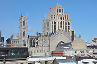 Basilique Notre-Dame de Montreal, with 2 bell towers and triple portal, built in 1823 in Gothic Revival style by James O'Donnell, and behind, the Aldred Building, an Art Deco office building designed by Ernest Isbell Barott and built 1929-31, seen from the Pointe-a-Calliere Museum, in Montreal, Quebec, Canada. The basilica is listed as a National Historic Site of Canada. Picture by Manuel Cohen
