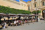 People at cafe tables next to National Library building, Republic Square, Valletta, Malta