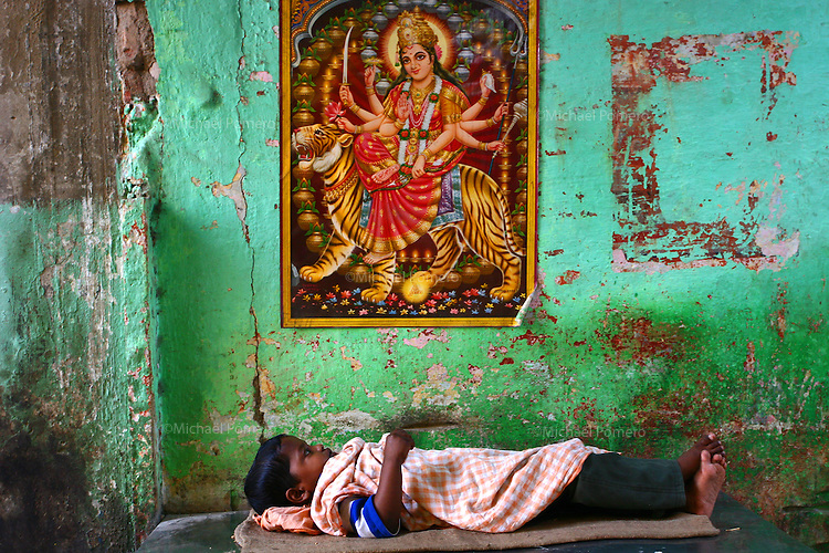 28.10.2007 Varanasi(Uttar Pradesh)<br /> <br /> Boy taking rest under godess Durga in the street.<br /> <br /> Enfant se reposant sous la d&eacute;esse Durga dans la rue.