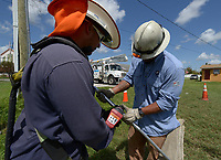 FPL linemen Antony Latour, left, and Alexander Romero, right splice a broken power line in South Miami-Dade county after Hurricane Irma Sept 12, 2017.  (Photo by David Adame/For FPL)