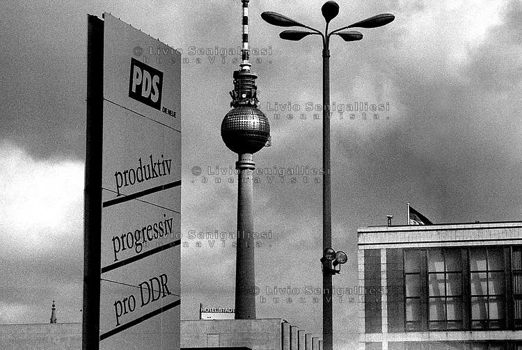 BERLINO EST / DDR / GERMANIA EST / 20 NOVEMBRE 1989.MANIFESTO PROPAGANDISTICO IN ALEXANDER PLATZ. SULLO SFONDO LA WOLKSKAMMER E LA TORRE DELLA TELEVISIONE..FOTO LIVIO SENIGALLIESI..EAST BERLIN / DDR / EAST GERMANY / 20 NOVEMBER 1989.BIG POSTER PRO-REGIME IN ALEXANDER PLATZ..ON THE BACKGROUND THE TELEVISION TOWER..PHOTO LIVIO SENIGALLIESI