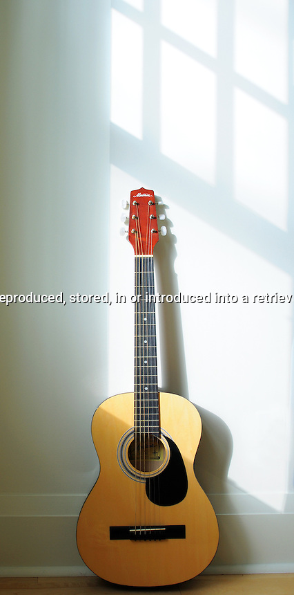 Acoustic Guitar leaning against a white wall