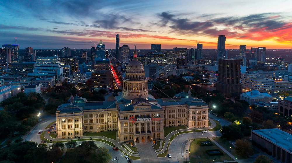 Aerial skyline view with golden sunset and dramatic sky over the Texas State Capitol Dome and building grounds, downtown Austin, Texas.