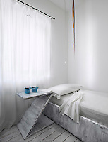 The simple wooden bedroom furniture, including a Z-shaped bedside table, has been given a rough coating of white paint the same as the floorboards