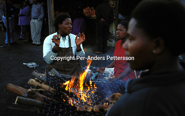 ditown00184 Township Women selling barbecued meat on fire on July 29, 2001 in Site B Khayelitsha, a township about 35 kilometers outside Cape Town, South Africa. Khayelitsha is one of the poorest and fastest growing townships in South Africa. People usually come from the rural areas in Eastern Cape province to find work as maids and laborers. Most people don't find work and the unemployment rate is very high, together with lot of violence and a growing HIV-Aids epidemic itÕs a harsh area to live in. Fire, food, vendor.Photo: Per-Anders Pettersson/iAfrika Photos..