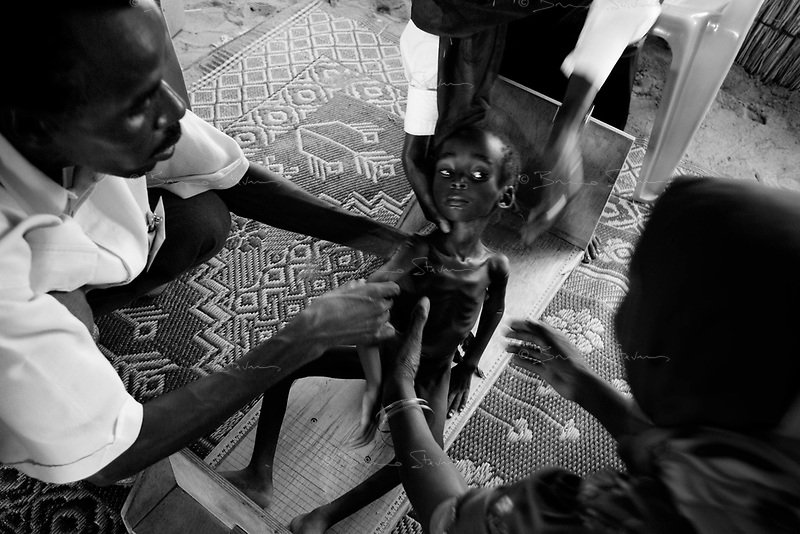 Kalma IDP camp, South Darfur, August 3, 2004.Tussa Abderahaman, 3 years old, is brought to an MSF emergency nutrition center in the camp, she suffers from severe malnutrition, weighing at only 6,3 kg .