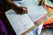 Mathumita fills up the CHDR (Child Health Development Record) for Tuvarny, the 10 month pregnant expecting woman before she leaves for the hospital as part of the pre-natal programme during the field visits in Punaineeravi village in Kilinochchi in Northern Sri Lanka. Photo: Sanjit Das/Panos