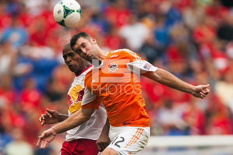 Will Bruin (12) of the Houston Dynamo goes up for a header with Jamison Olave (4) of the New York Red Bulls. The New York Red Bulls defeated the Houston Dynamo 2-0 during a Major League Soccer (MLS) match at Red Bull Arena in Harrison, NJ, on June 30, 2013.
