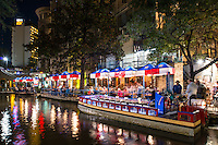 San Antonio river walk dinning on the tour boats at night in downtown.  This tour boat was being set up for a party at the Republic of Texas restaurant along the river walk.  Dinning on the water.