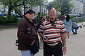 Paris, France. 09.05.2015. A couple pose for photos, outside Notre Dame, with a pigeon on the man's head. Photograph © Jane Hobson