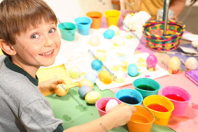 Photo of smiling young boy coloring Easter eggs with several cups of eggs in different, brightly colored dye.