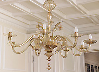 The flowing shapes of a Murano glass chandelier create an eye catching feature in the formal dining room
