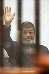FILE PHOTO: Former Egyptian president Mohamed Morsi gestures from the defendants cage as he attends his trial at the police academy on the outskirts of the capital, on June 10, 2015. Former President Mohamed Morsi died on Monday in court after the conclusion of a trial session in the espionage lawsuit, Egyptian state TV said. Photo by Amr Sayed