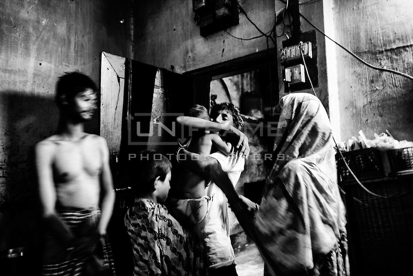 After coming back home from a one month long boxing workshop, Zakir hugs his nephew. Zakir and his six family members live in this house which consists in only one room. Khilgong, Dhaka. Bangladesh.