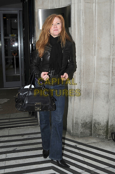 CAROL DECKER (T'Pau).leaving the BBC Radio 2 London, England, UK, 18th November 2010..full length black leather jacket bag jeans scarf flared flares .CAP/IA.©Ian Allis/Capital Pictures.
