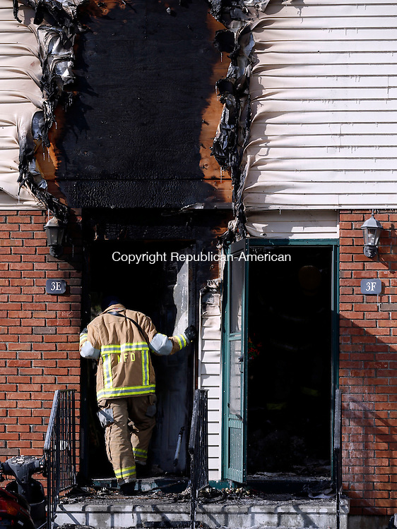 Naugatuck, CT- 13 February 2016-021316CM03- A firefighter surveys a room inside the scene of a fire at Meadowland Estates in Naugatuck on Saturday.  Multiple condos were destroyed by fire and others were heavily damaged by smoke at the complex, which is off Horton Hill Road in south end of the borough.       Christopher Massa Republican-American