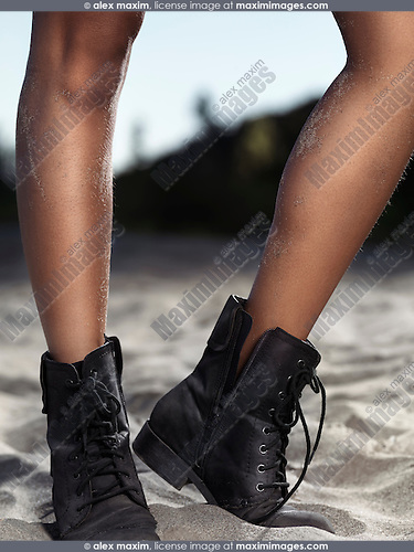 Young woman legs in black leather boots standing in sand at the beach