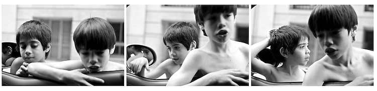 I was waiting in the corner (inside my car) at the red light, when these two kids approaached me.  They were clearing commingup from the beach, shirtless with a beach ball.  I took a 3 exposures, and then they saw I had some coins right by the shift.  When I gave them 10 Uruguayan Pesos each (1 USD), they both said 'two crackers each' (dos galletas para cada uno).  ..Street photography with a Leica M8 in Montevideo, Uruguay.