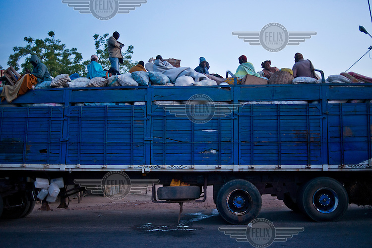 A lorry traveling towards the desert pulling a trailer loaded with sacks and passengers.