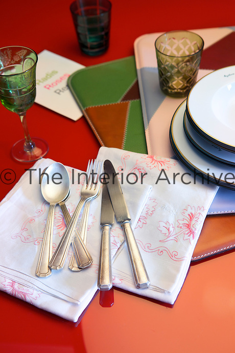 On the red lacquered glass and steel dining table the cutlery, crockery and glassware are a mixture of style and period