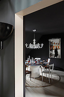In the dramatic black and white dining room the walls are panelled in black papier mache with a photograph by Pierre-Henri Chauveau and the floor is of polished concrete
