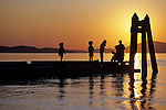 Silhouetted family fishing on dock at sunset Washington Park Anacortes Washington State USA..