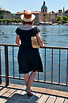 A woman in a black dress and wearing a straw hat looks across the water at Como, Italy