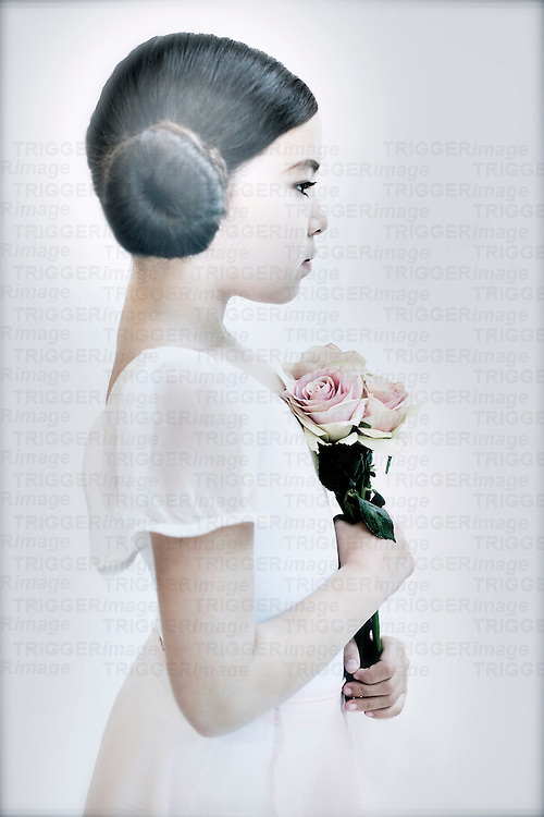 Young girl with dark hair standing holding roses