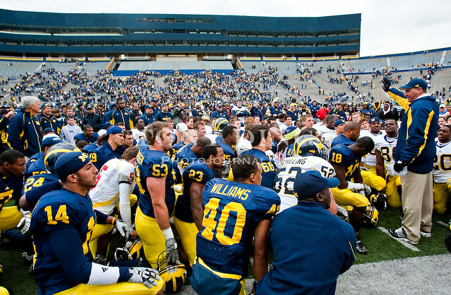 Michigan head coach Rich Rodriguez, right, speaks to his team on the Michigan Stadium turf after the Wolverines' spring football game, Saturday, April 17, 2010, in Ann Arbor, Mich. The Big House is finishing up construction on major renovations, including a new press box scheduled for completion by the start of the 2010 season. (AP Photo/Tony Ding)