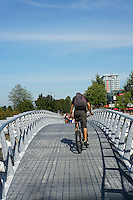 Cyclist crossing  the Canoe Bridge in the Olympic Village area, Vancouver, BC, Canada